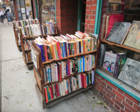 A cart full of books stationed outside a storefront