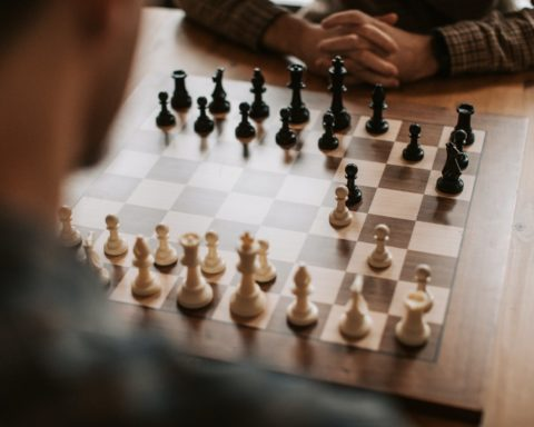 A chess board with only two pawns moved forward, with a child's arms folder in waiting